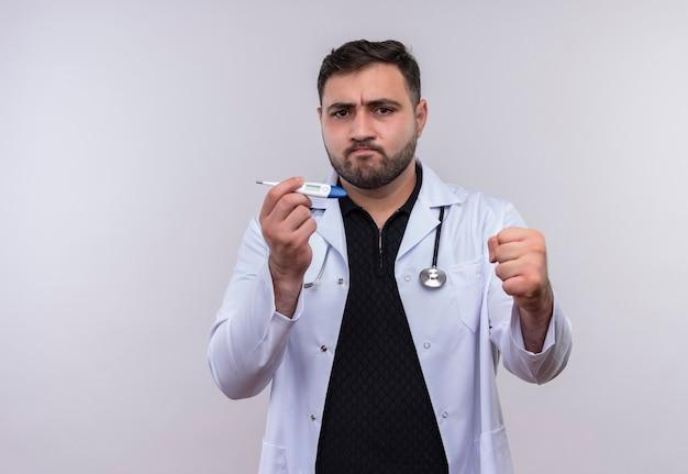 Młody brodaty mężczyzna lekarz ubrany w biały fartuch ze stetoskopem trzymając cyfrowy termometr uśmiechnięty pewny siebie zaciskając pięść, koncepcja zwycięzcy