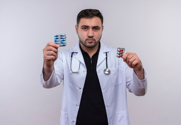 Młody brodaty mężczyzna lekarz ubrany w biały fartuch ze stetoskopem, trzymając pęcherze z pigułkami, pokazano do kamery z poważną miną