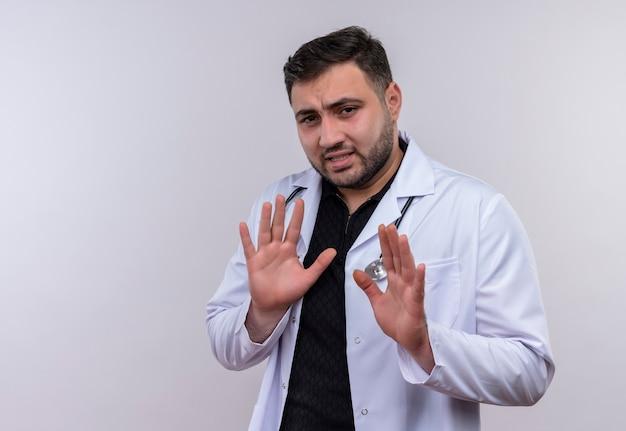 Młody brodaty mężczyzna lekarz ubrany w biały fartuch ze stetoskopem, trzymając się za ręce, czyniąc gest obrony z niesmakiem