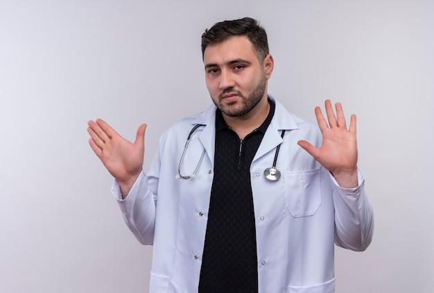 Młody brodaty mężczyzna lekarz ubrany w biały fartuch ze stetoskopem, trzymając się za ręce, czyniąc gest obrony z wyrazem strachu