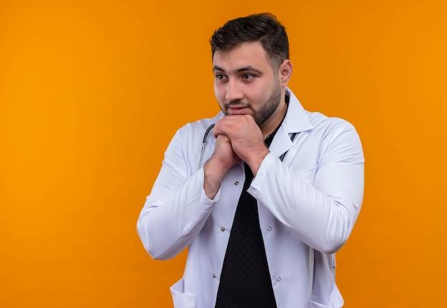 Młody brodaty mężczyzna lekarz ubrany w biały fartuch ze stetoskopem, trzymając się za ręce razem patrząc na bok emocjonalny i zaskoczony