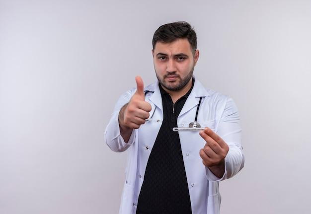 Młody brodaty mężczyzna lekarz ubrany w biały fartuch ze stetoskopem trzymając termometr patrząc na kamery pokazując kciuk do góry z radosną buźką