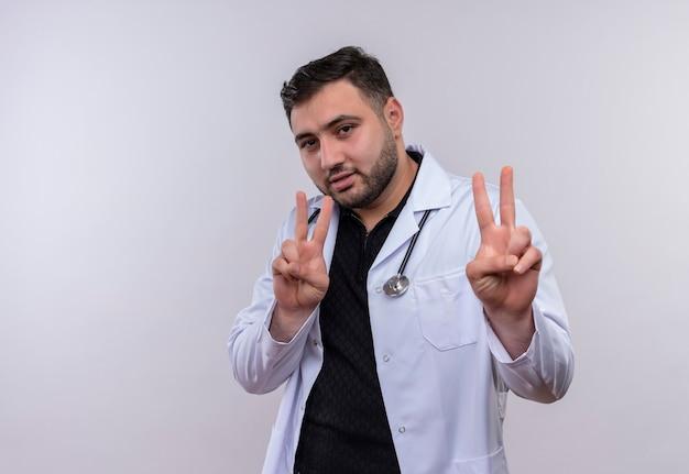 Młody brodaty mężczyzna lekarz ubrany w biały fartuch ze stetoskopem, uśmiechając się pewnie, pokazując znaki zwycięstwa obiema rękami
