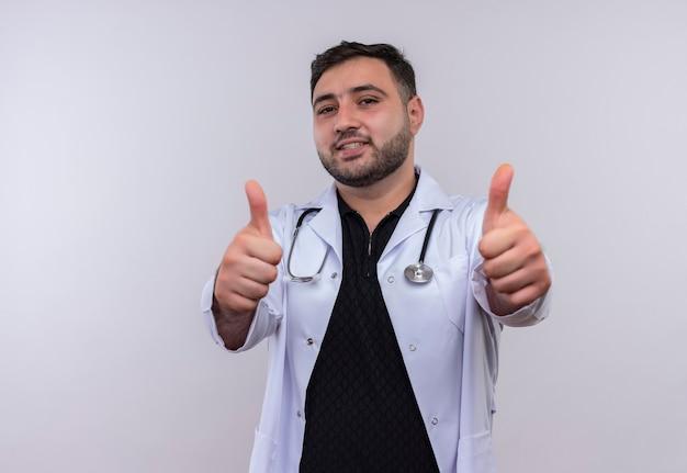 Młody brodaty mężczyzna lekarz ubrany w biały fartuch ze stetoskopem uśmiechnięty pokazując kciuki obiema rękami