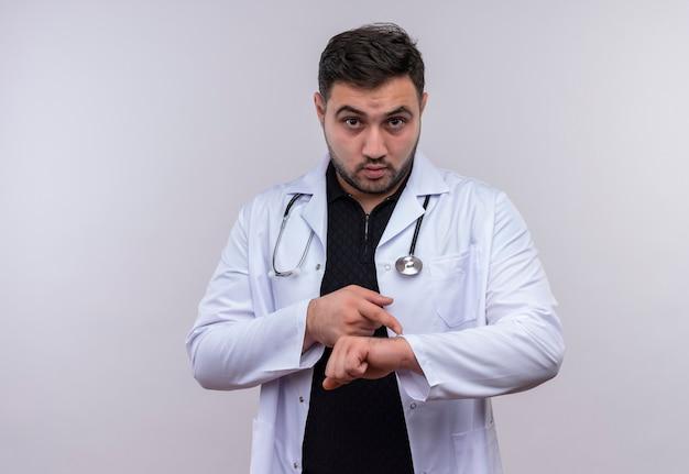 Młody brodaty mężczyzna lekarz ubrany w biały fartuch ze stetoskopem wskazującym na dłoń, przypominając o zmartwieniu czasu