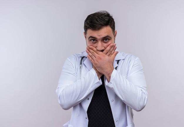 Młody brodaty mężczyzna lekarz ubrany w biały fartuch ze stetoskopem wstrząśnięty zakrywając usta dłońmi borh