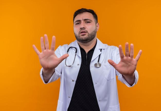 Młody brodaty mężczyzna lekarz ubrany w biały fartuch ze stetoskopem wyciągając ręce co znak stopu z wyrazem strachu