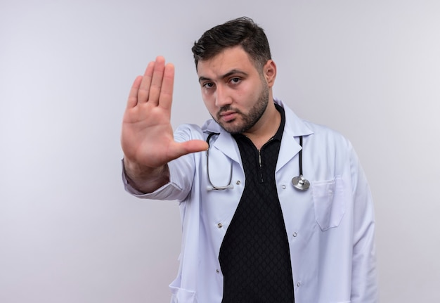 Młody brodaty mężczyzna lekarz ubrany w biały fartuch ze stetoskopem z otwartymi rękami co znak stopu z poważną miną
