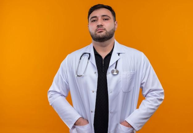 Młody brodaty mężczyzna lekarz ubrany w biały fartuch ze stetoskopem z rękami w kieszeniach patrząc pewnie