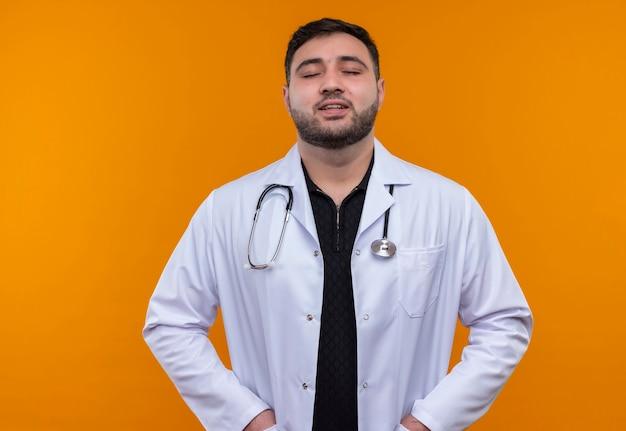 Młody brodaty mężczyzna lekarz ubrany w biały fartuch ze stetoskopem z rękami w kieszeniach uśmiechnięty