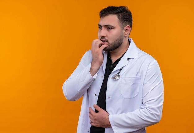 Młody brodaty mężczyzna lekarz ubrany w biały fartuch ze stetoskopem zestresowany i nerwowo obgryzający paznokcie