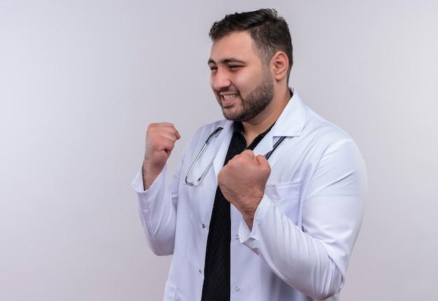 Młody brodaty mężczyzna lekarz ubrany w biały płaszcz ze stetoskopem, patrząc na bok, pozujący jak bokser z zaciśniętymi pięściami uśmiechnięty, koncepcja zwycięzcy