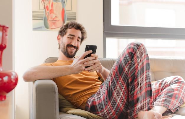 Młody brodaty mężczyzna na kanapie z inteligentny telefon