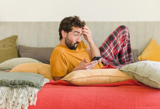 Młody brodaty mężczyzna na łóżku z telefonem komórkowym