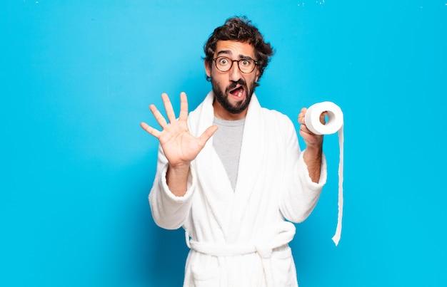 Młody brodaty mężczyzna na sobie szlafrok i rolę toalety