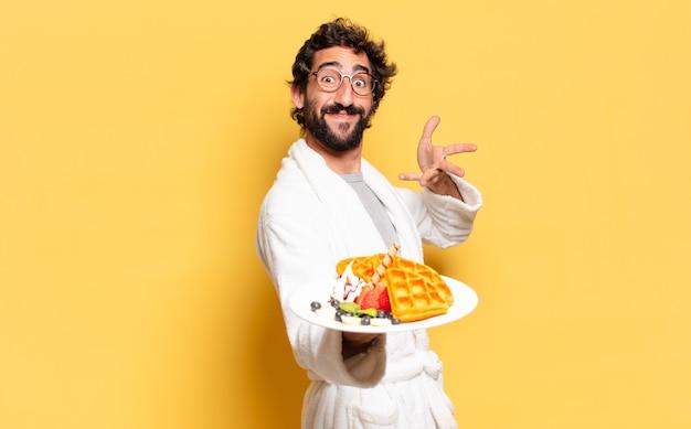 Młody brodaty mężczyzna na sobie szlafrok i śniadanie