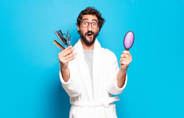 Młody brodaty mężczyzna na sobie szlafrok i trzymając narzędzia fryzjerskie
