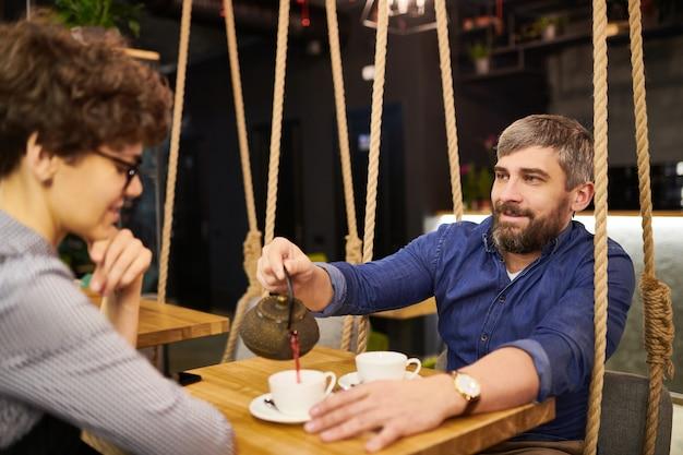 Młody brodaty mężczyzna nalewania herbaty w filiżance dla swojej dziewczyny podczas randki w wygodnej kawiarni lub restauracji