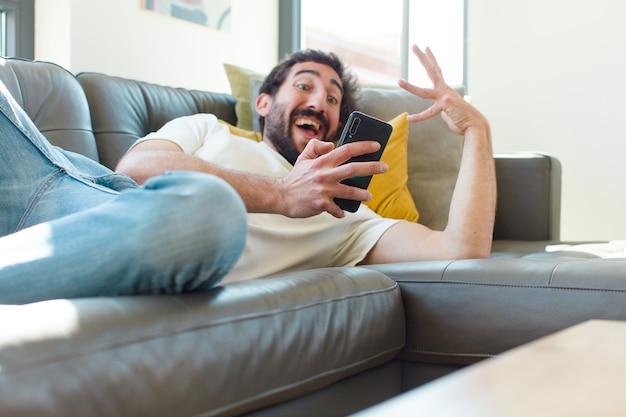Młody brodaty mężczyzna odpoczywa na kanapie ze swoim smartfonem