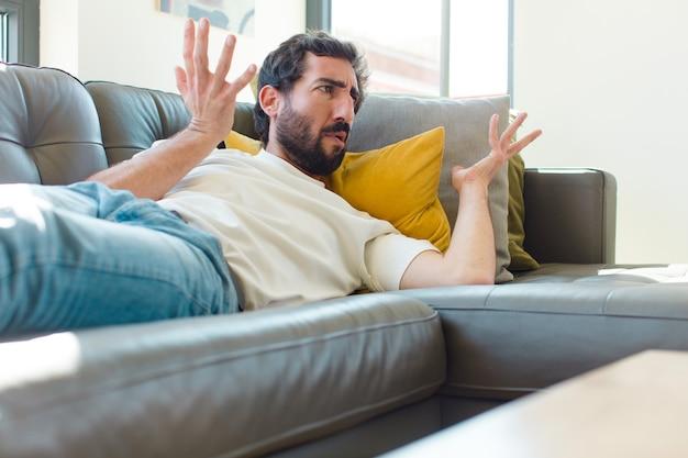 Młody brodaty mężczyzna odpoczywa na kanapie