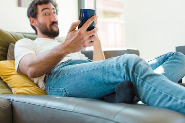 Młody brodaty mężczyzna odpoczywający na kanapie ze smartfonem