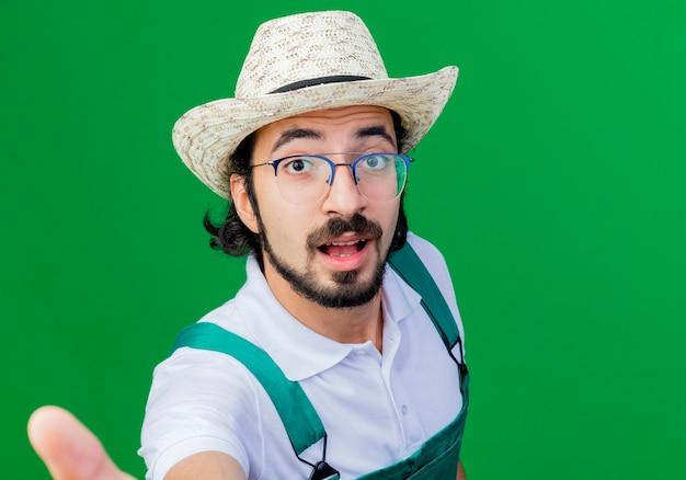 Młody brodaty mężczyzna ogrodnik na sobie kombinezon i kapelusz patrząc z przodu uśmiechnięty z szczęśliwą twarzą stojącą nad zieloną ścianą
