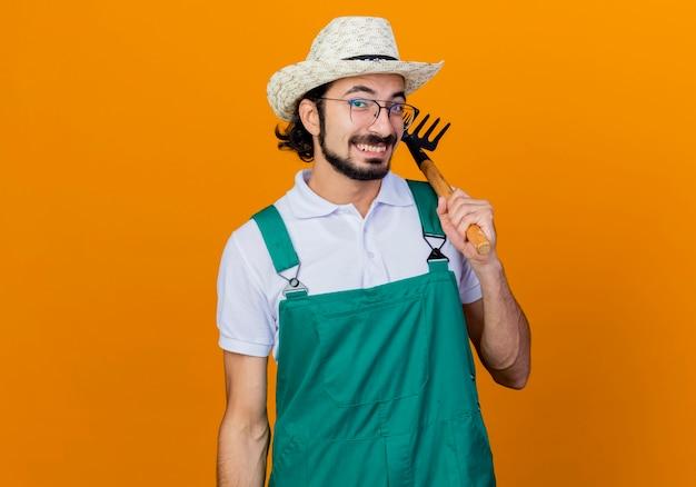 Młody brodaty mężczyzna ogrodnik na sobie kombinezon i kapelusz trzymając mini prowizji patrząc na przód uśmiechnięty z radosną twarzą stojącą nad pomarańczową ścianą