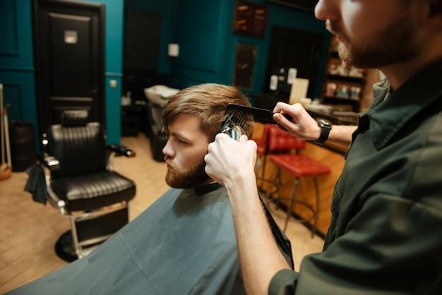 Młody brodaty mężczyzna ostrzyżony przez fryzjera elektryczną maszynką do golenia siedząc na krześle