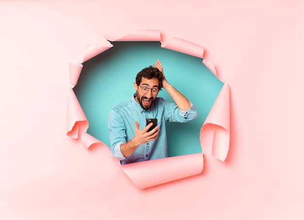 Młody brodaty mężczyzna patrzący na telefon