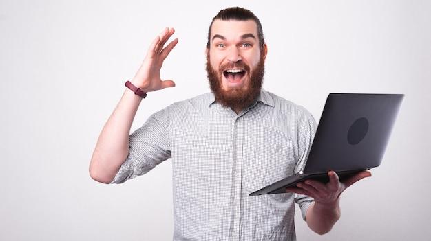 Młody brodaty mężczyzna patrzy podekscytowany na aparat trzymając laptopa w pobliżu białej ściany
