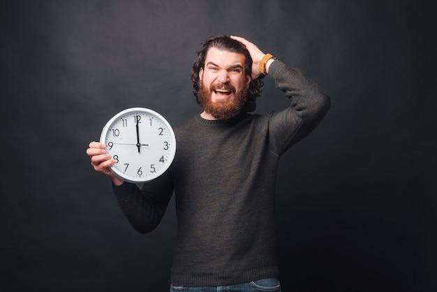 Młody brodaty mężczyzna patrzy zestresowany trzymając zegar ścienny