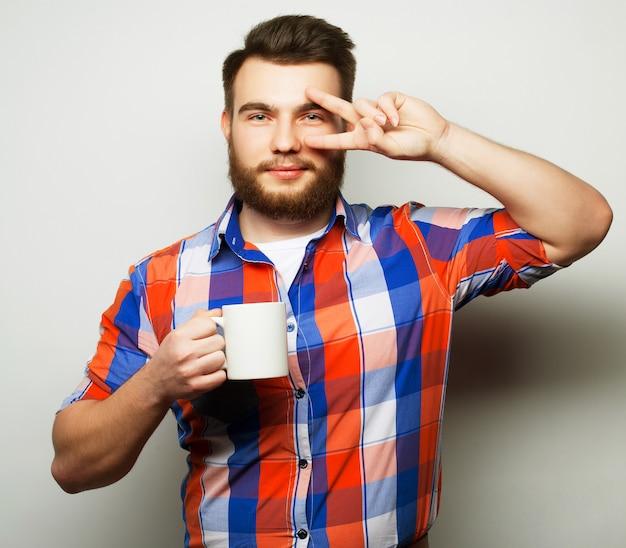 Młody brodaty mężczyzna pije filiżankę kawy lub herbaty