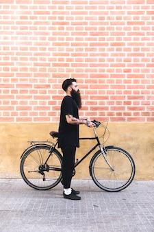 Młody brodaty mężczyzna pije kawę podczas gdy stojący na jego bicyklu outdoors