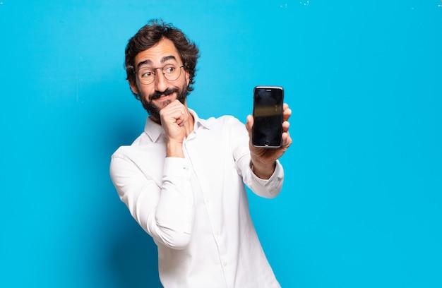 Młody brodaty mężczyzna pokazuje ekran swojej komórki