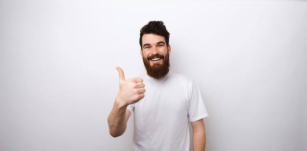 Młody brodaty mężczyzna pokazuje jak gest z kciukiem up.