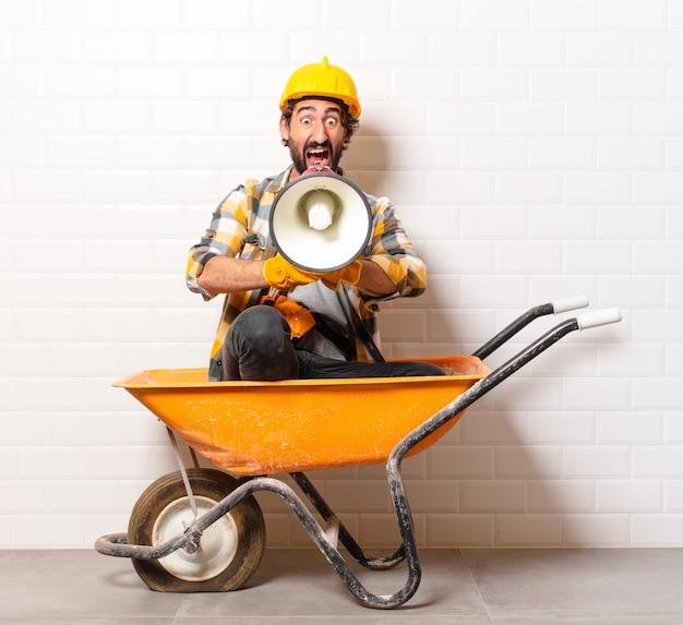 Młody brodaty mężczyzna pracownik budowlany na taczce