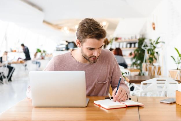 Młody brodaty mężczyzna pracujący na laptopie siedząc w kawiarni w pomieszczeniu