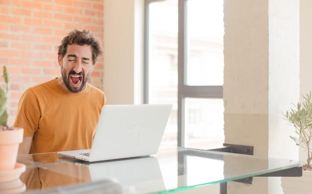 Młody brodaty mężczyzna pracujący w domu z laptopem