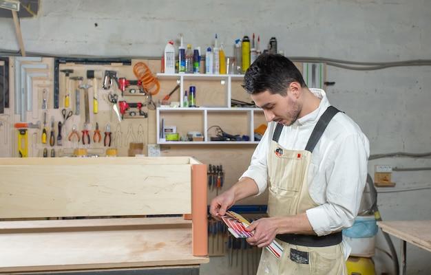 Młody brodaty mężczyzna pracujący w fabryce mebli, dopasowywanie kolorów do mebli.
