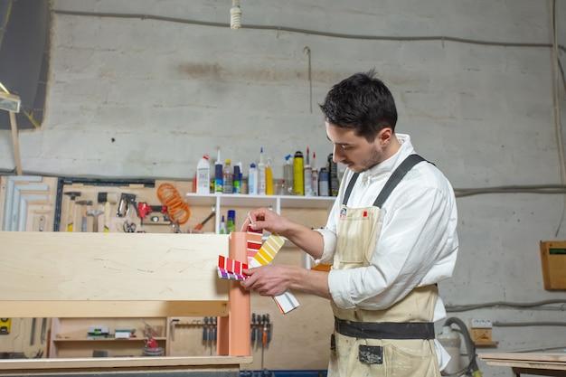 Młody brodaty mężczyzna pracujący w fabryce mebli, dopasowywanie kolorów do mebli