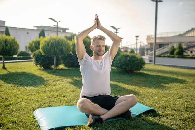 Młody brodaty mężczyzna praktykuje jogę na zewnątrz, podnosząc ręce nad głową