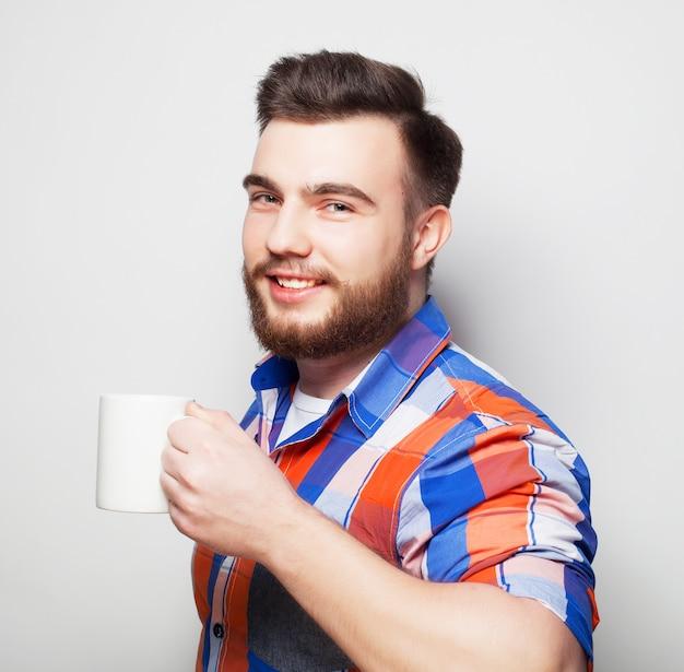 Młody brodaty mężczyzna przy filiżance kawy