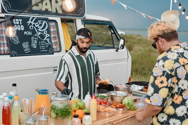 Młody brodaty mężczyzna przygotowuje fast food dla ludzi na plaży w słoneczny dzień