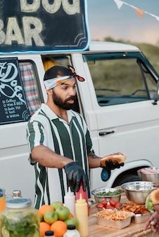 Młody brodaty mężczyzna przygotowuje fast food na plaży z kawiarnianą furgonetką w tle
