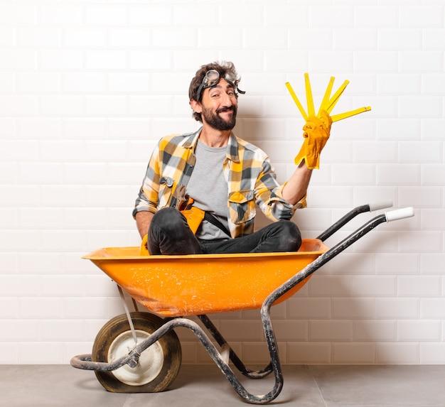 Młody brodaty mężczyzna robotnik budowlany na taczce