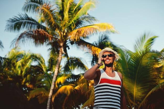 Młody brodaty mężczyzna rozmawia na smartfonie na tle palm