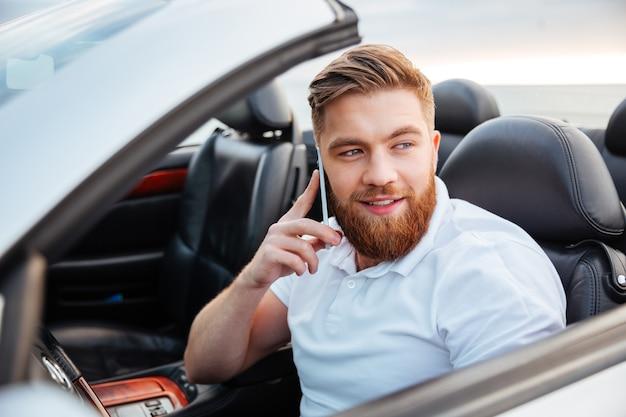 Młody brodaty mężczyzna rozmawia przez telefon i prowadzi samochód kabriolet