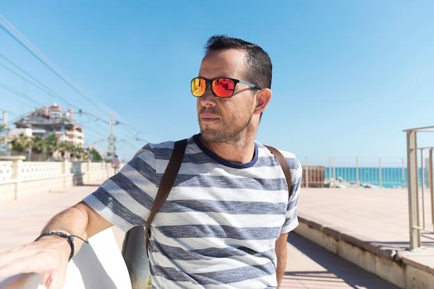 Młody brodaty mężczyzna siedzi na deptaku z okularami przeciwsłonecznymi podczas gdy patrzejący daleko od