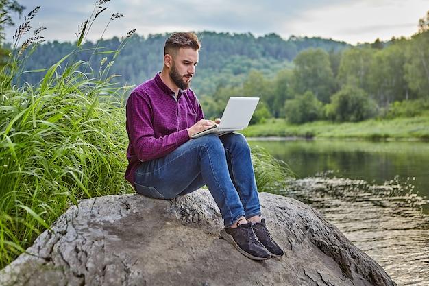Młody brodaty mężczyzna siedzi na kamieniu w pobliżu rzeki z laptopem na kolanach, patrzy na ekran i wpisuje tekst na klawiaturze.