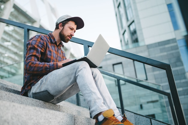 Młody brodaty mężczyzna siedzi na schodach stadionu z laptopem